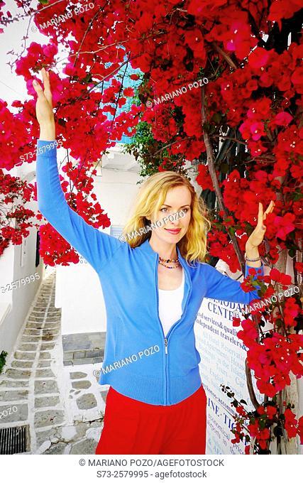 Woman in Mykonos front a buganvilia plant, Cyclades Islands, Greece