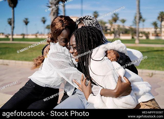 Happy teenage girlfriends hugging outdoors