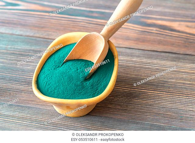 Bowl of spirulina on the wooden table