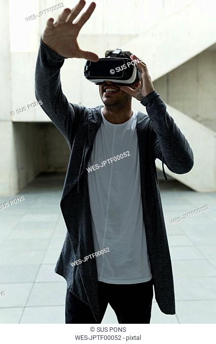 Young man wearing Virtual Reality Glasses raising his hand