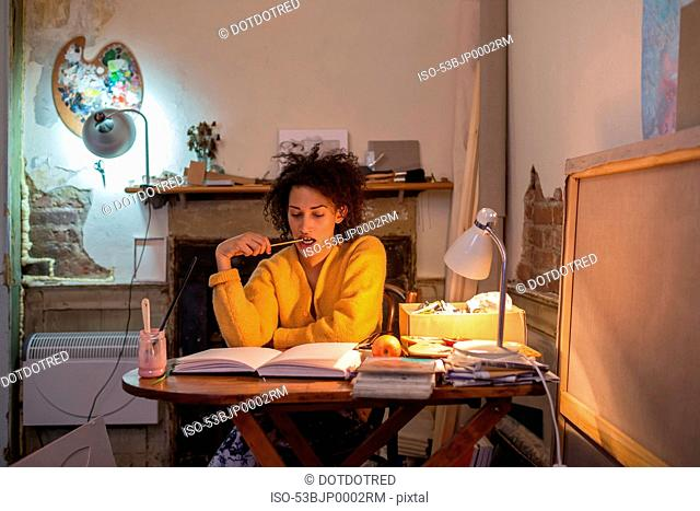 Woman reading book at desk