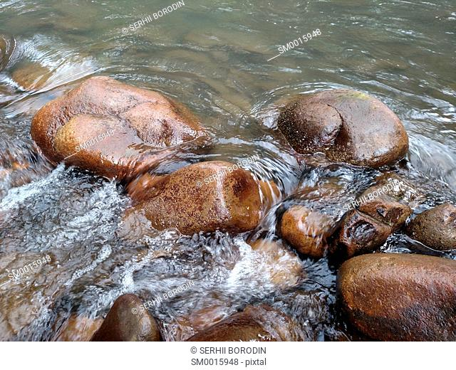 Water flowing over stones Boulders washed by river fluid Amazing water-cascade over natural rocks nature