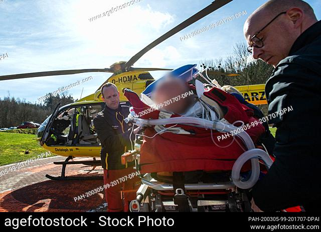 02 March 2020, Lower Saxony, Wolfenbüttel: The helicopter pilot Christian Schälicke (l) and the emergency paramedic Martin Losse drive a patient to the...