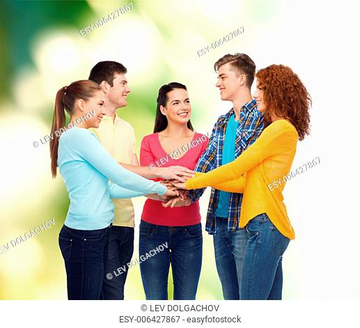 friendship, ecology, gesture, teamwork and people concept - group of smiling teenagers putting hand on top of each other over green background