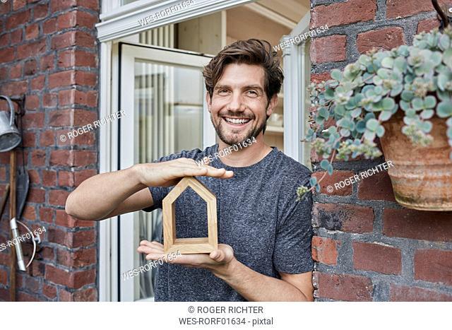 Portrait of smiling man at house entrance holding house model