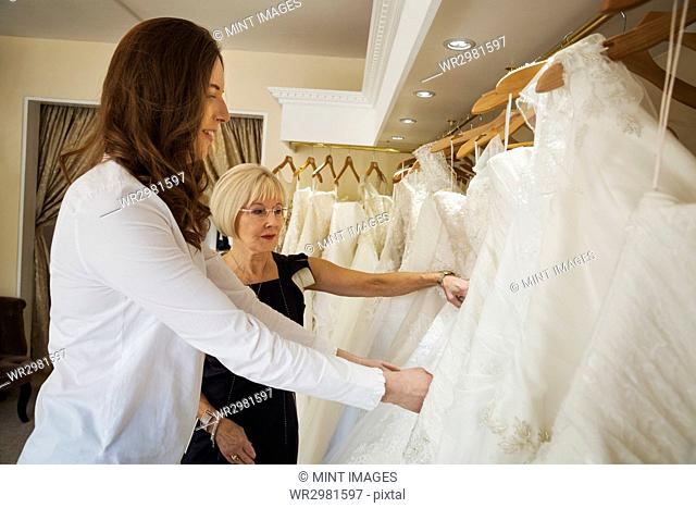 Two women, a young bride to be and a mature sales assistant looking through rails of wedding dresses