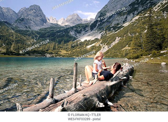 Austria, Tyrol, playful mother and daughter on tree trunk at lake Seebensee