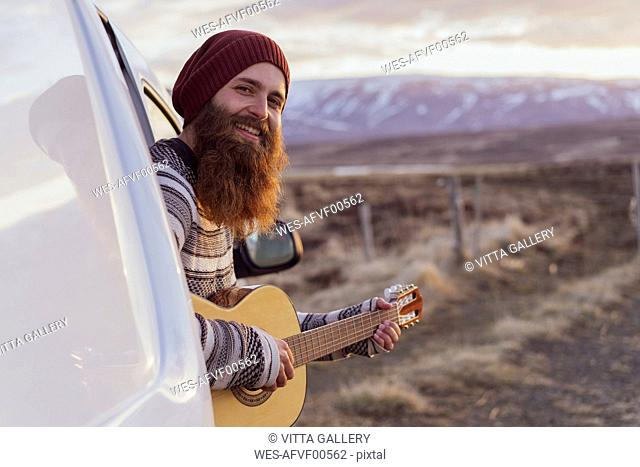 Iceland, young man sitting in van and playing guitar