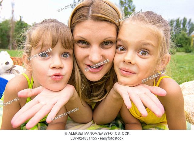 Two girls resting her head on her mother's palm and fun look into the frame