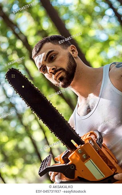 portrait of aggressive muscular male lumberjack, woodworker with chainsaw in hand, posing