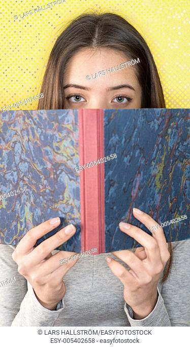 Serious and beautiful teenage girl reading book