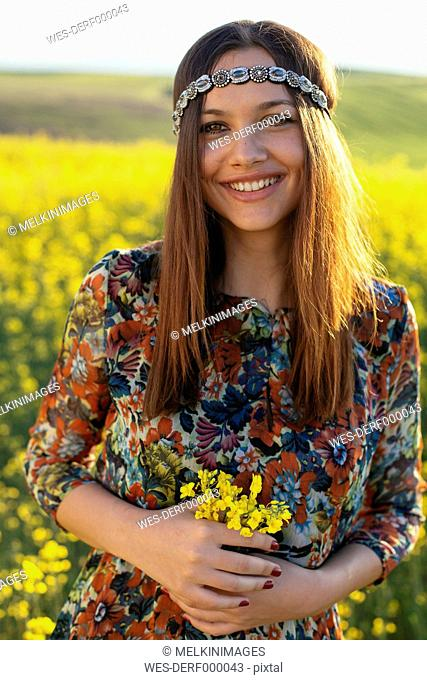 Portrait of smiling young hippie standing in a rape field holding flowers