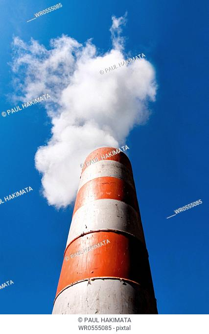 Red orange with white industrial smokestack with toxic carbondioxide CO2 fume smoke exhaust blowing into the blue sky