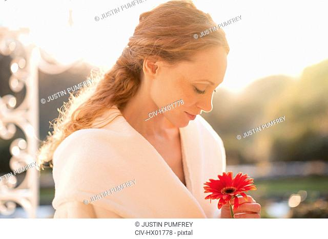 Serene woman holding red gerbera daisy on sunny patio