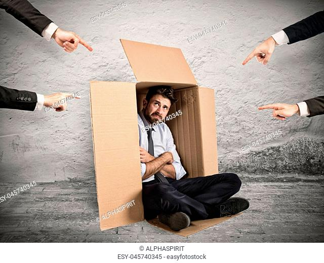 Businessman indicated by colleagues hiding in a cardboard