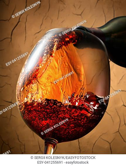 Red wine pouring into wineglass on clay background