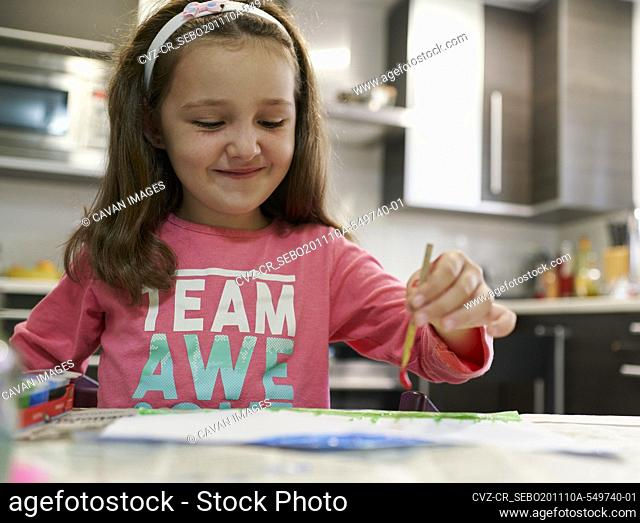 Little girl painting a drawing with watercolors inside her house with a kitchen in the background. Creative concept
