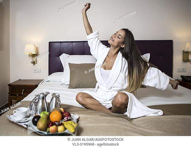 Beautiful woman with dark hair in white morning gown sitting on bed and stretching with plate of fruits and coffee set placed near