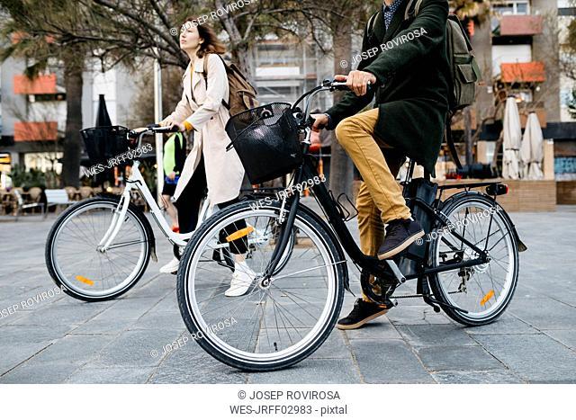 Couple riding e-bikes in the city
