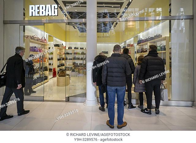New York NY/USA-December 19, 2018 Curious tourists look inside the window of the newly opened Rebag store in the World Trade Center Transportation Hub