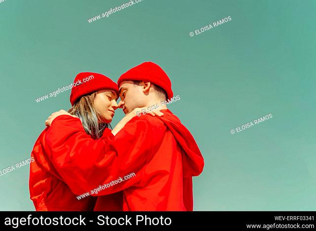 Young couple wearing red overalls and hats standing head to head against sky
