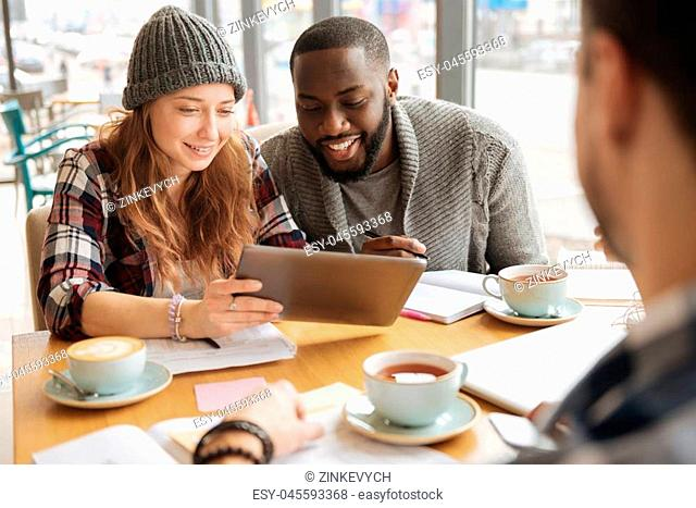 Watching funny videos. Nice pretty woman holding modern tablet and sharing some information with her fellow during studying process at cafe