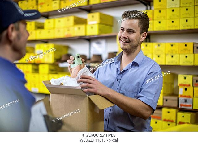 Man in warehouse checking delivered cardboard box