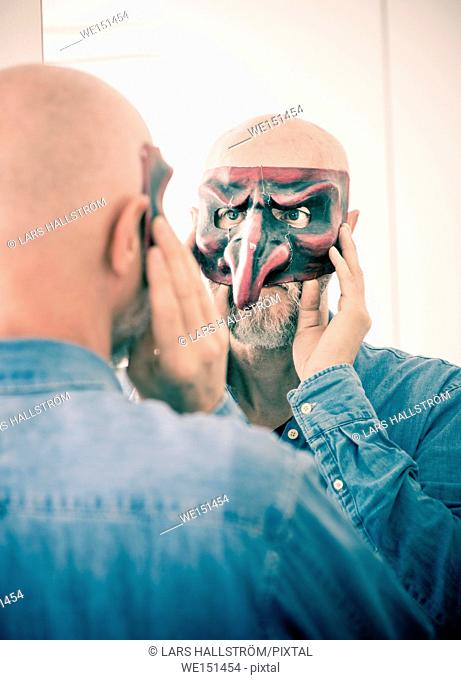 Old man cover face with carnival mask. Looking at himself in a mirror. Concept of ageing, self image as a senior person and hiding identity