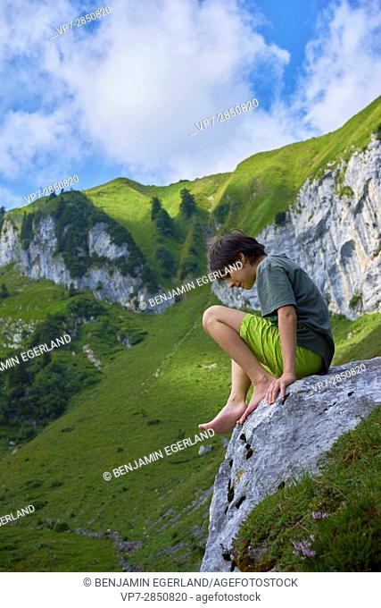 young thoughtful male child sitting on rock enjoying nature during dreamlike hiking adventure in the Bavarian mountains, Brauneck, Germany