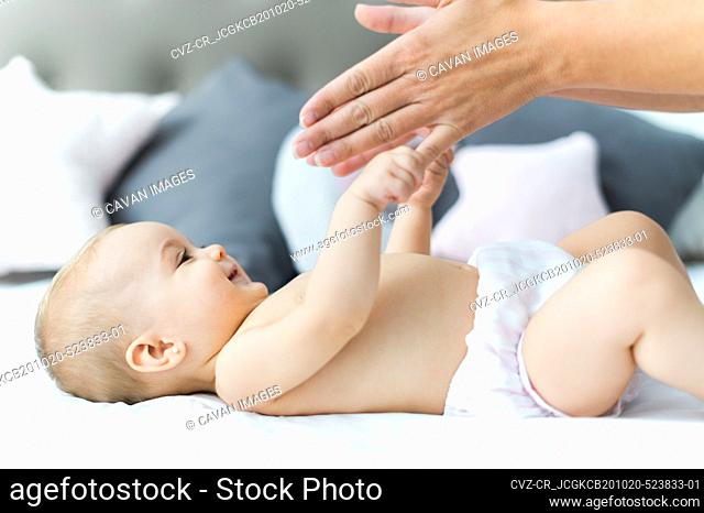 BEAUTIFUL BABY LYING ON THE BED PLAYING WITH MOM
