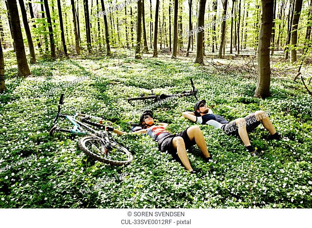 Mountain bikers relaxing in forest
