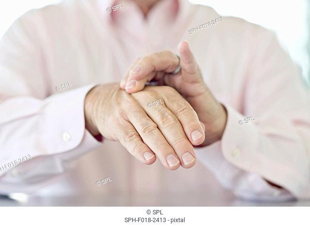 Senior man rubbing painful hand