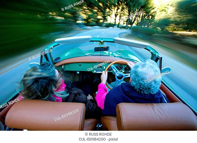Rear view of senior couple speeding on rural road driving vintage convertible, Majorca, Spain