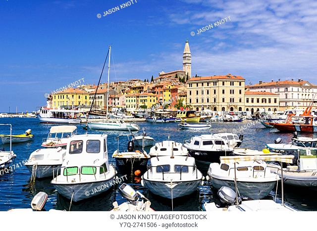 Moored boats overlooked by the colourful buildings of the old town peninsular of Rovinj, Istria, Croatia