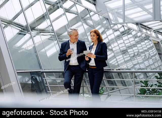 Smiling businessman and businesswoman talking in modern office building