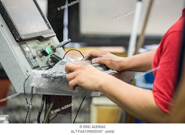 Factory worker using machine in factory