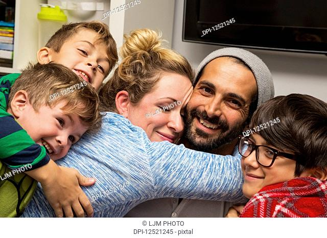 A family of five in a close embrace; Langley, British Columbia, Canada