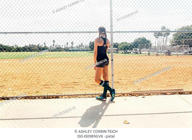 Schoolgirl soccer player at wire fence on school sports field