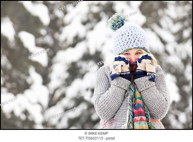 USA, Utah, Salt Lake City, portrait of young woman in winter clothing covering mouth