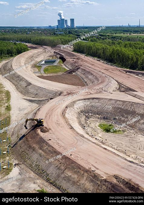 23 June 2020, Saxony, Rötha: An excavator is working on the future Böhlen-Zwenkau junction (aerial photograph with drone)