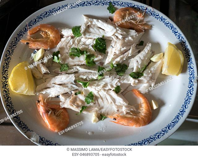 dish of sea bass and shrimp with parsley and lemon