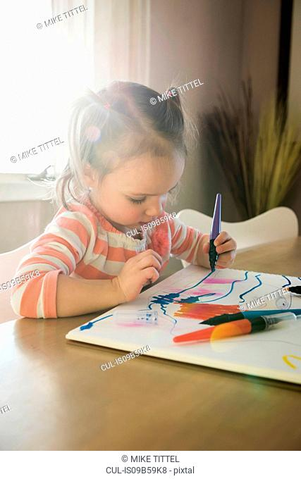 Female toddler at table drawing in sketchbook