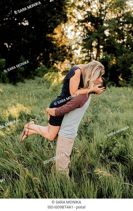 Romantic man lifting up girlfriend in field of long grass