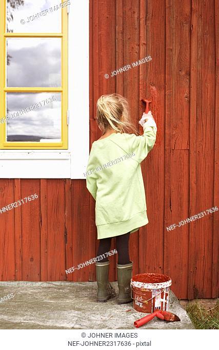 Girl painting wooden house
