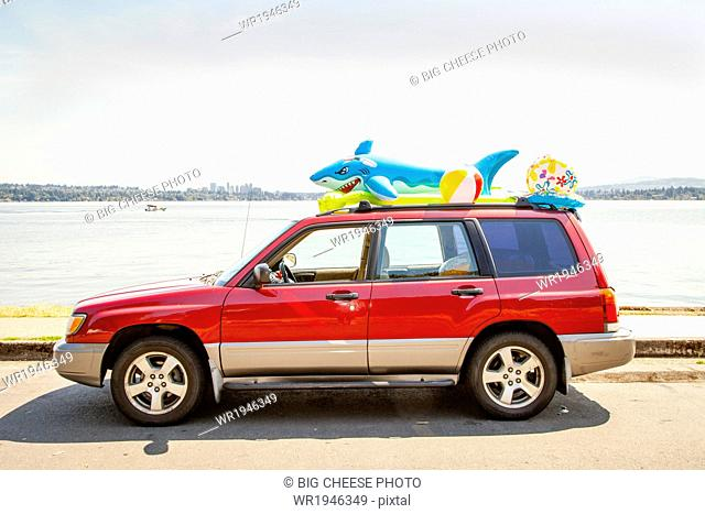 Car with beach toys and floaties on the roof parked by a lake