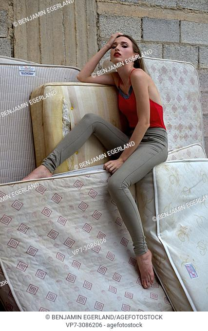 model woman sitting on mattresses, thoughtful, tired, sensual, exhausted
