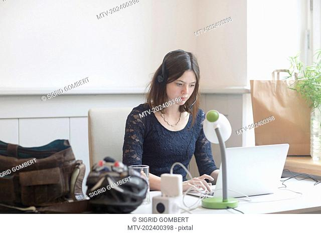 Businesswoman working on laptop in an office, Freiburg Im Breisgau, Baden-Württemberg, Germany
