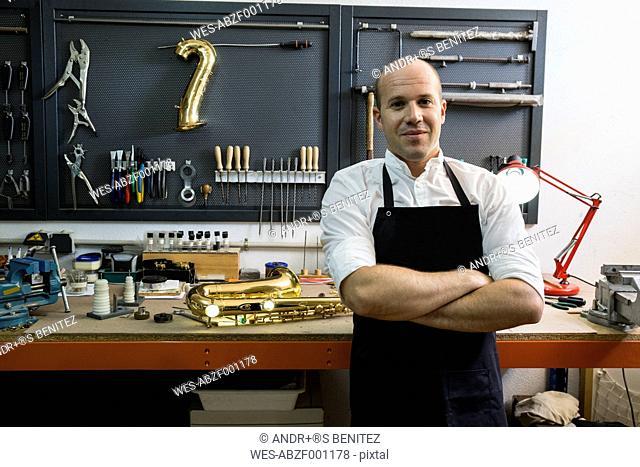 Portrait of a confident instrument maker in his workshop