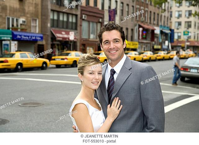 A bride and groom posing on a Manhattan street