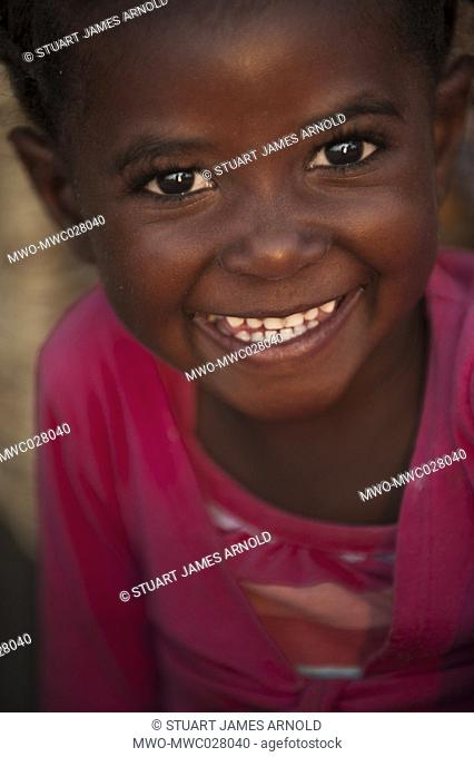 Big smile, big eyes, happy young gild child in a pink top